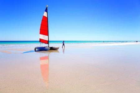 Sailing Catamaran Pulled Up On Beach and Woman Walking Away